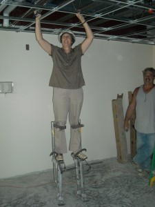 Sr. Betty Schuster on Stilts Inspecting at the newly-renovated House of Blessing in Warren